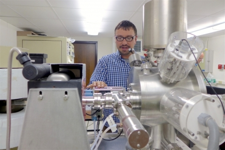 Aaron Satkoski, a scientist in the Department of Geoscience at UW–Madison, with the mass spectrometer used to measure isotopes in rocks from South Africa. DAVID TENENBAUM